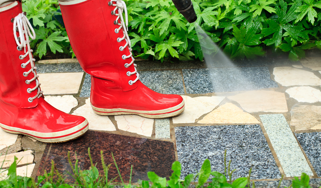 A person in red boots pressure washing a walkway